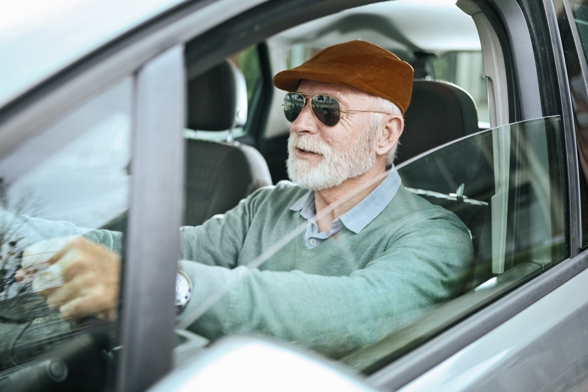 Senior man sitting in car driving
