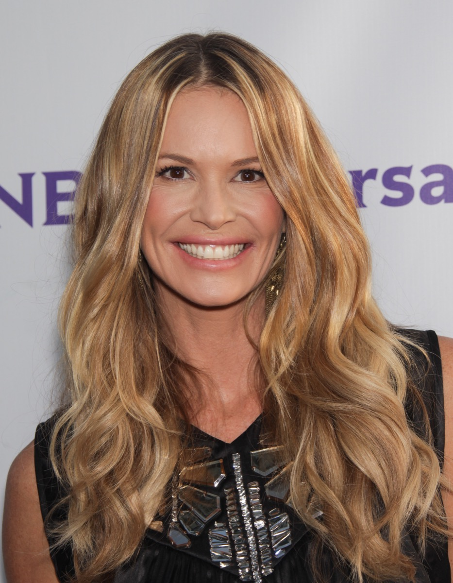 elle macpherson stands in front of an NBCUniversal step and repeat in a black outfit