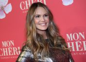 elle macpherson in a shiny gold dress in front of a red step-and-repeat