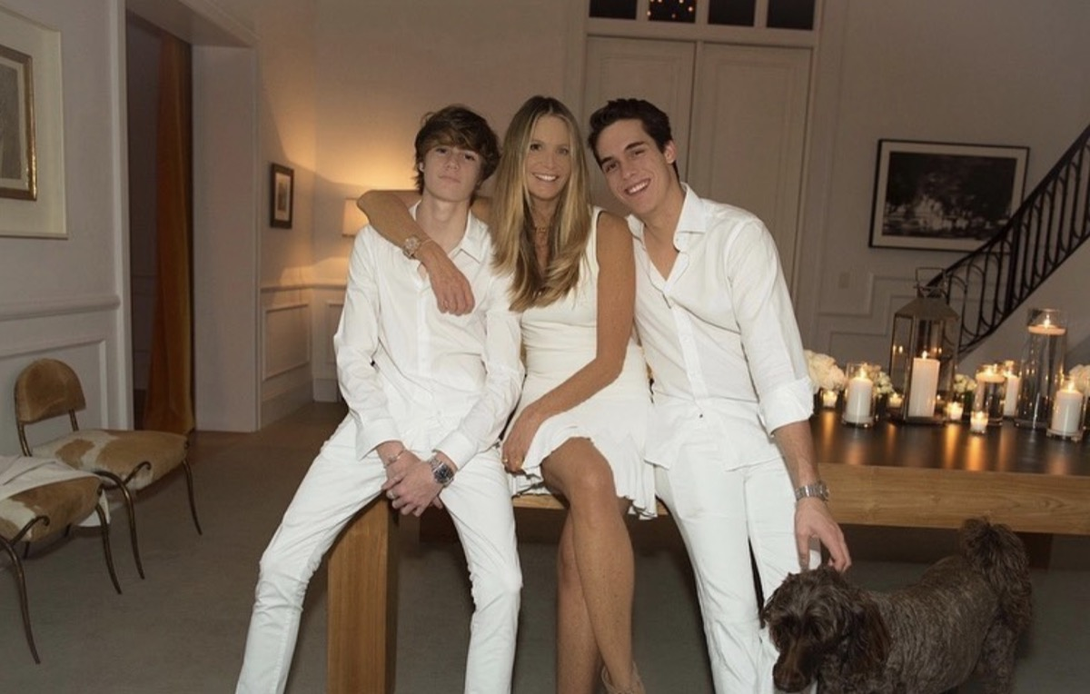 elle macpherson and her two sons wearing all white and sitting on a table next to a brown dog