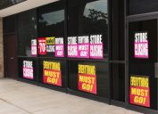 Horizontal angled shot of the windows of a store plastered with going out of business signs