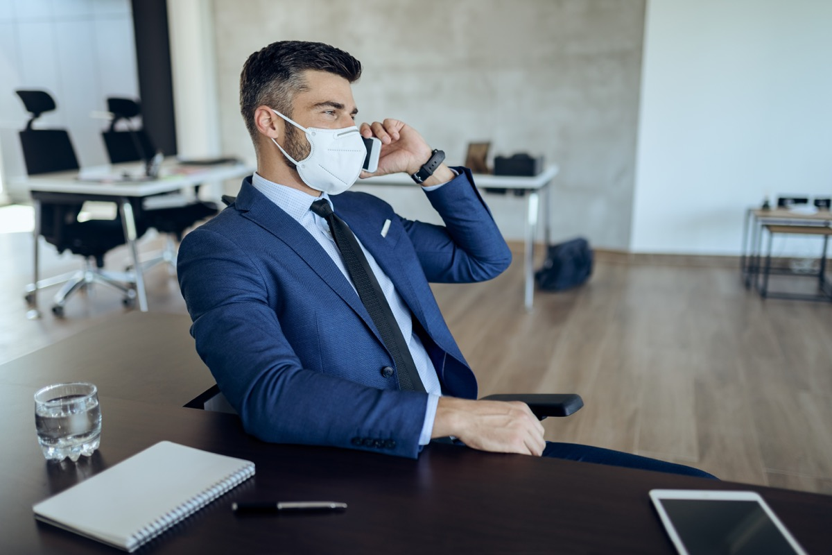 Businessman with face mask talking on smart phone while working in the office during coronavirus epidemic.