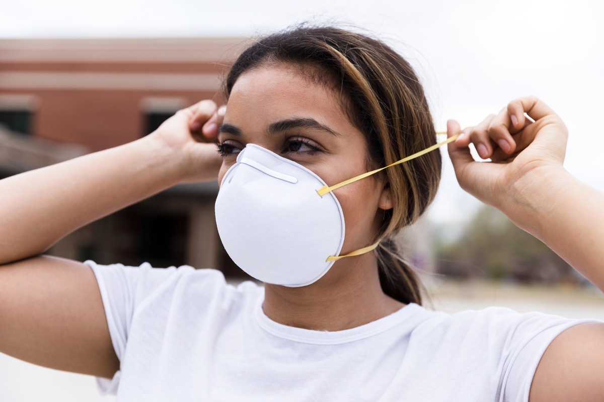 During a pandemic, a mid adult woman protects herself by placing an N95 face mask over her nose and mouth. She is standing outdoors.