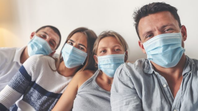 A group of four brothers and sisters sits smiling while wearing surgical masks