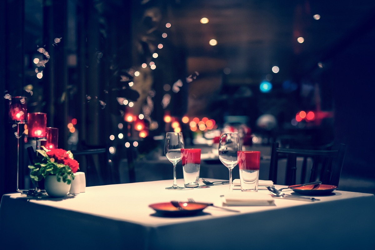A fancy dinner set up with red decorations and a candle