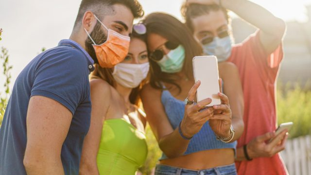 Happy Friends with protective safety mask having fun making selfies during coronavirus (COVID 19) pandemic in the summer.