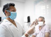 Male nurse preparing vaccine using face mask