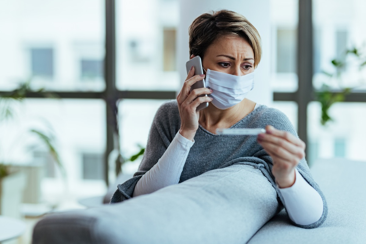 Distraught woman wearing face mask and measuring temperature while communicating on mobile phone at home.