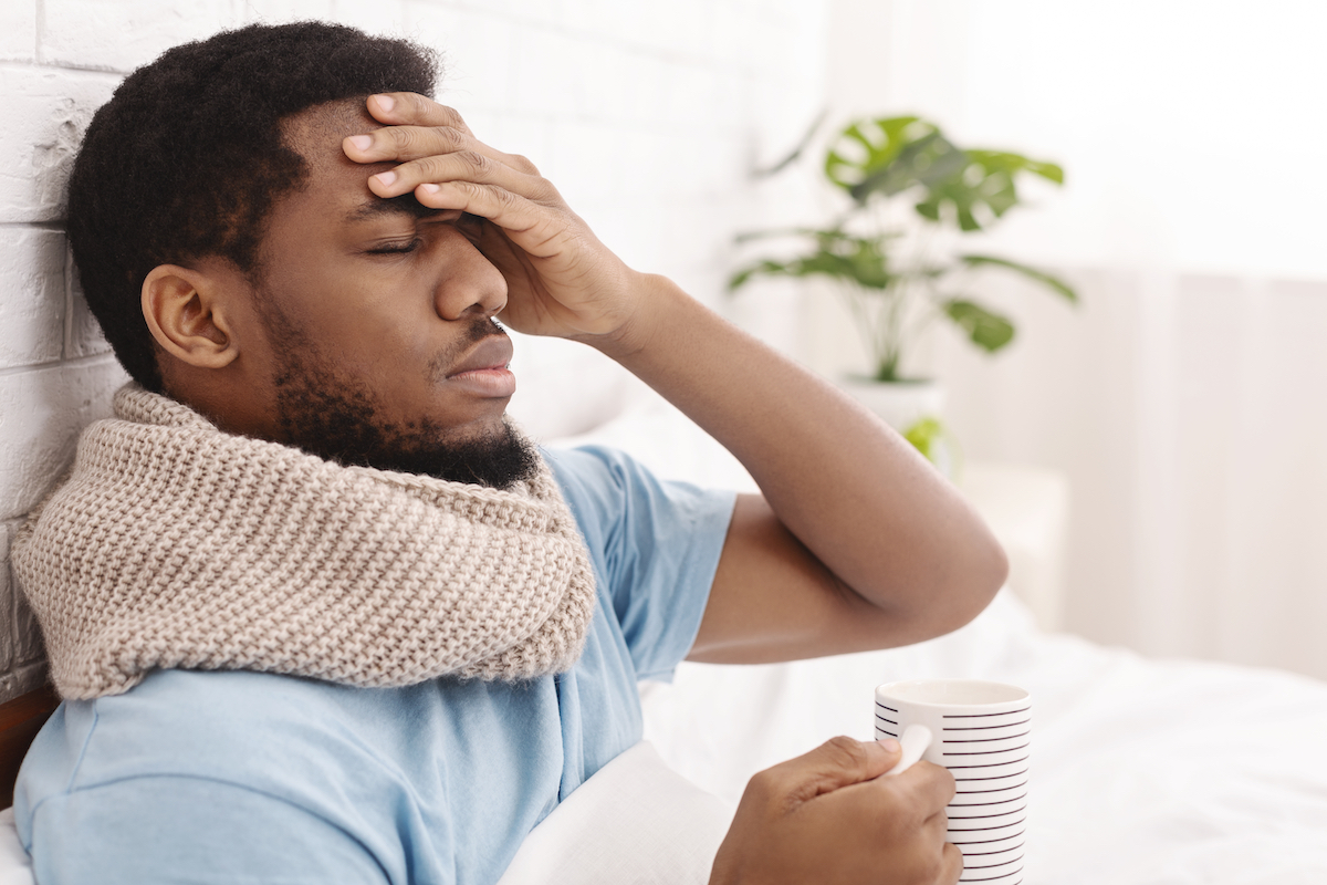 Sick man having fever, drinking hot tea and touching forehead