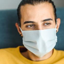 Young man wearing a protective medical face mask and feeling apathetic. Indoor photo. Coronavirus protection / staying at home during quarantine concept.