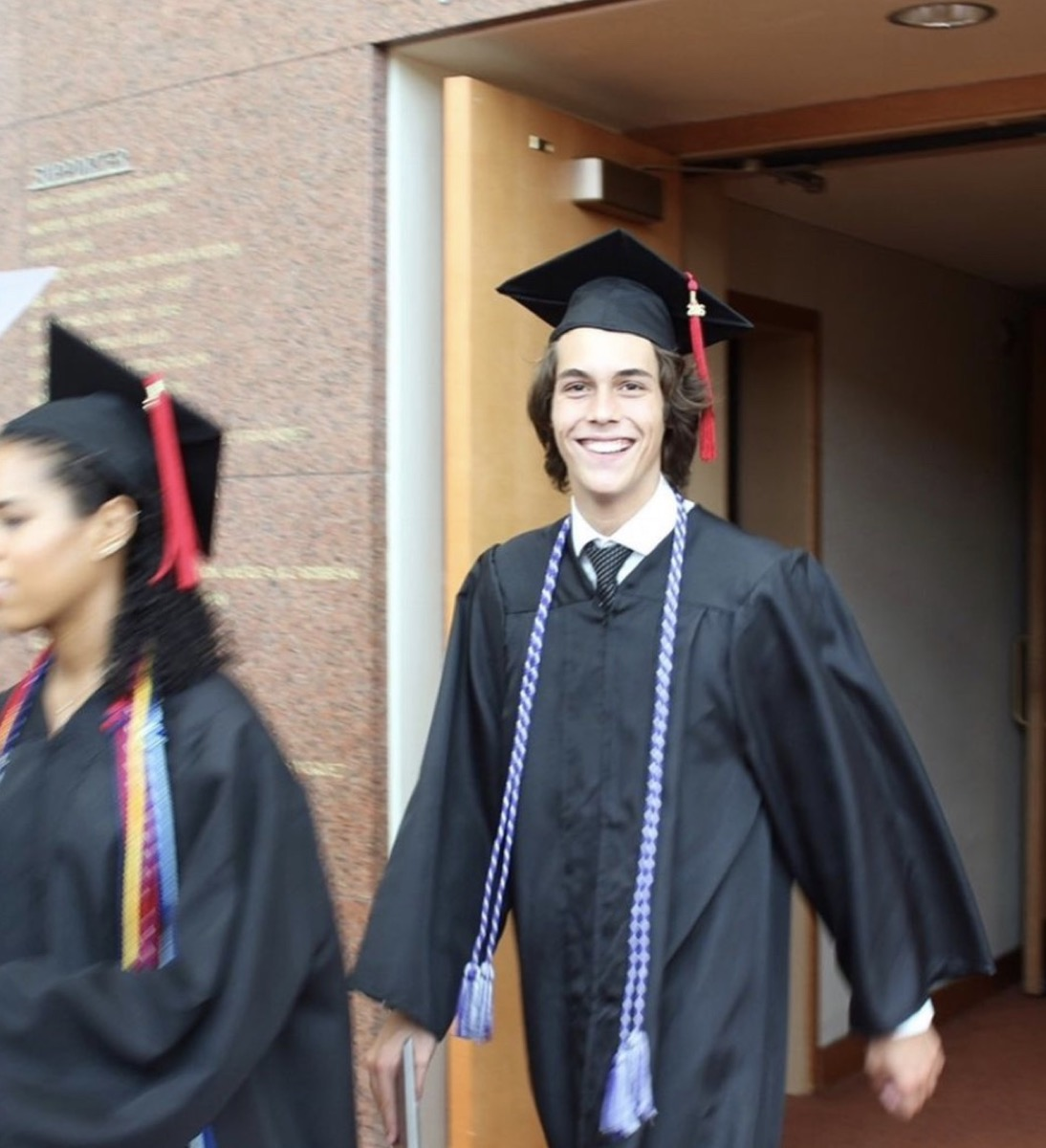 flynn busson in cap and gown emerging from a brick building