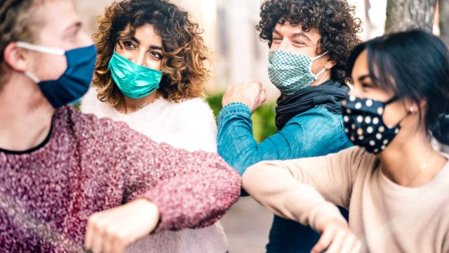 Friends greeting with elbow bump wearing face protection – New normal lifestyle concept with young people covered by disposable mask – Selective focus on middle left woman