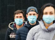 A group of three young people wearing face masks and winter coats stand in a line.