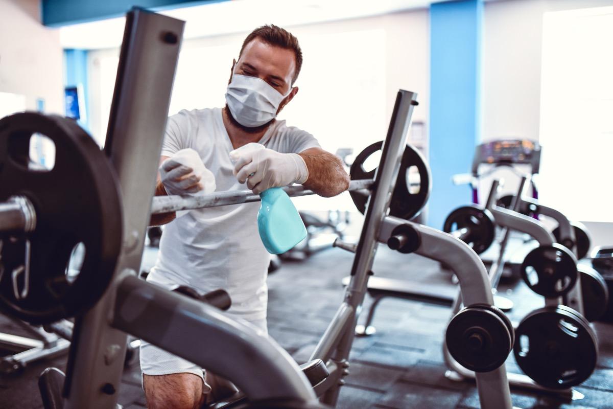 Gym Worker Disinfecting Barbell Rack To Prevent Coronavirus Spread