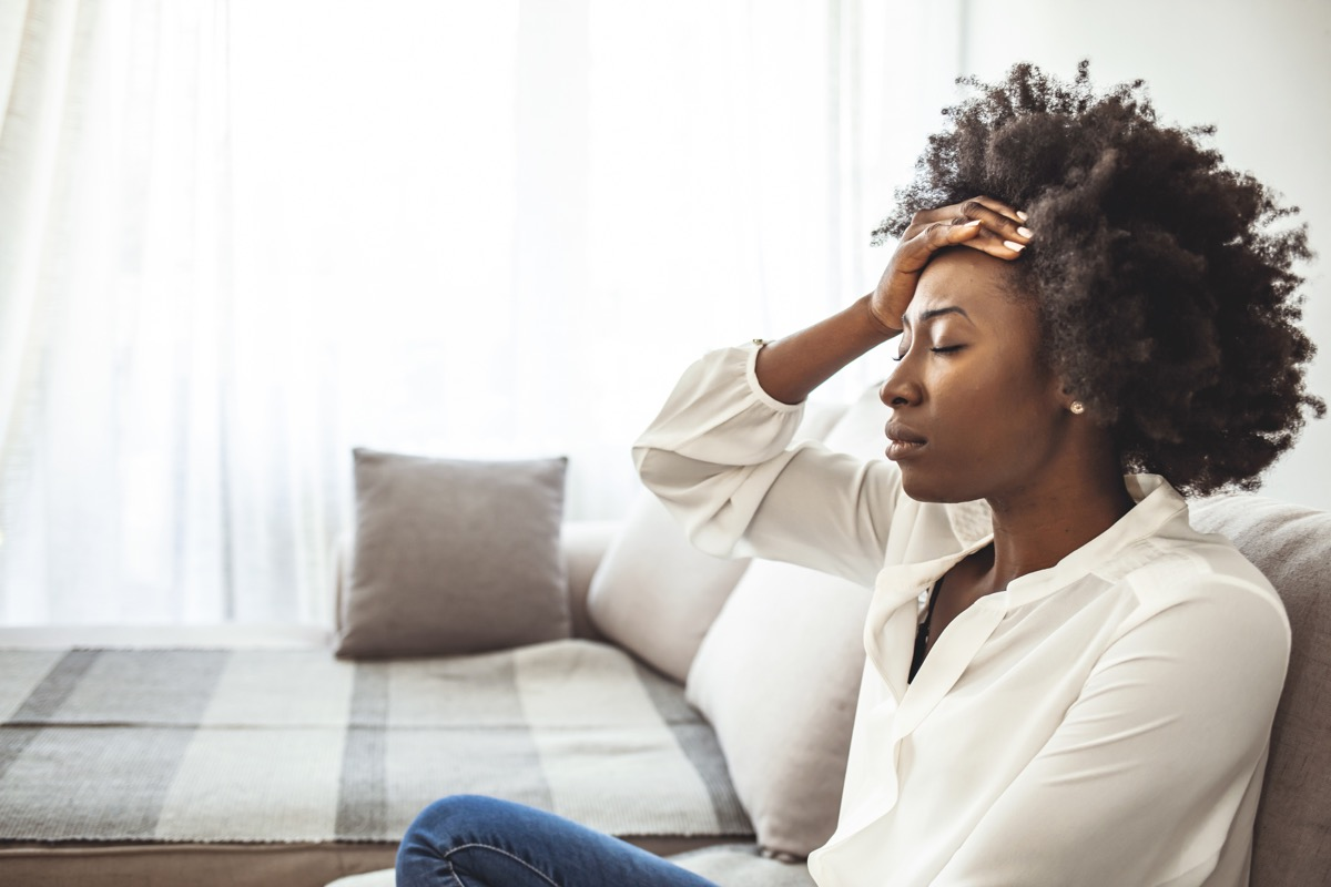 Lonely sad woman deep in thoughts sitting daydreaming or waiting for someone in the living room with a serious expression, she is pensive and suffering from insomnia sitting on couch (Lonely sad woman deep in thoughts sitting daydreaming or waiting fo