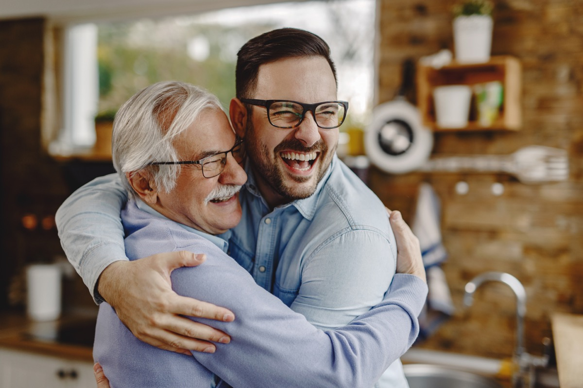 Happy mature man having fun while embracing with his adult son who came to visit him.
