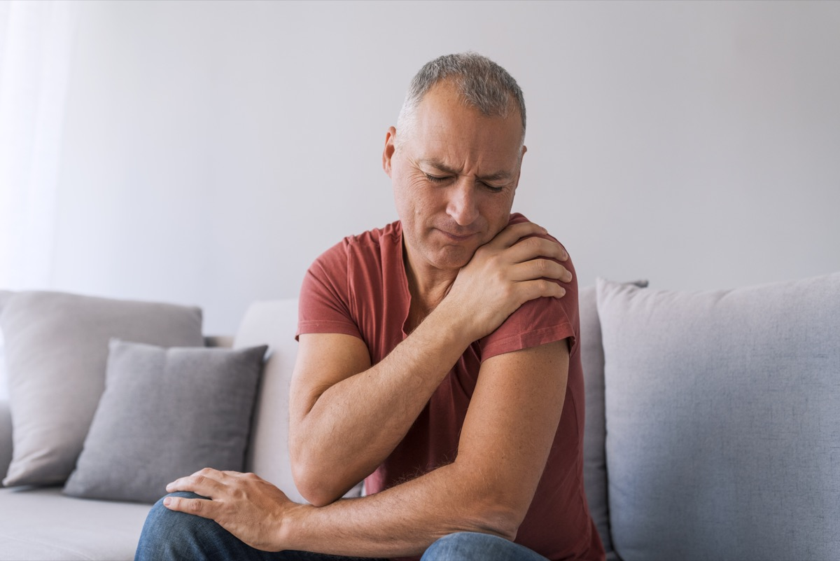 Photo of mature man suffering from pain in shoulder, closeup. People, healthcare and problem concept - unhappy man suffering from neck or shoulder pain at home. Shoulder pain Caused by not taking care of health.