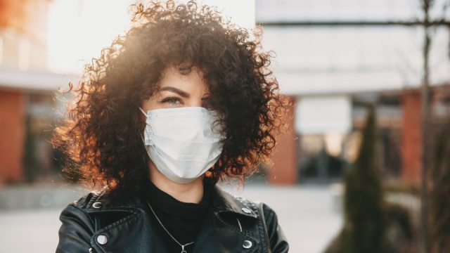 Trying to prevent a flu and is wearing a white protective mask