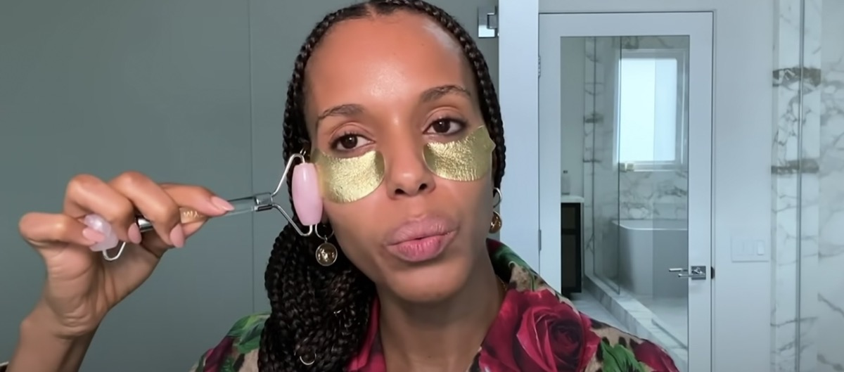 kerry washington wearing gold undereye patches and using a jade roller with her hair in a braid
