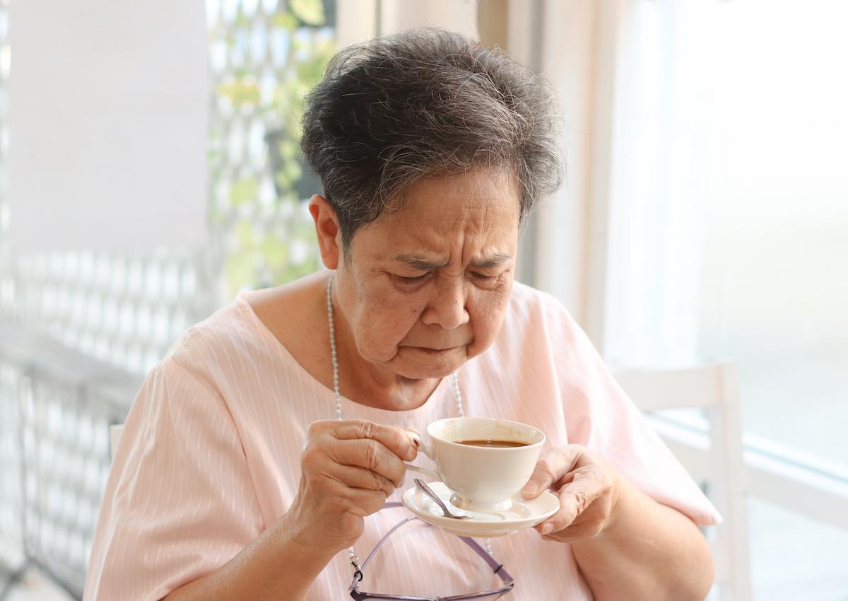 Senior woman tasting bitter coffee