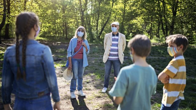 likely to give you Covid Grandparents and grandchildren meeting in the park. The COVID-19 pandemic restrictions are loosened and the seniors are allowed to see their grandchildren with keeping distance and wearing masks. BMPCC4K, raw, Q0