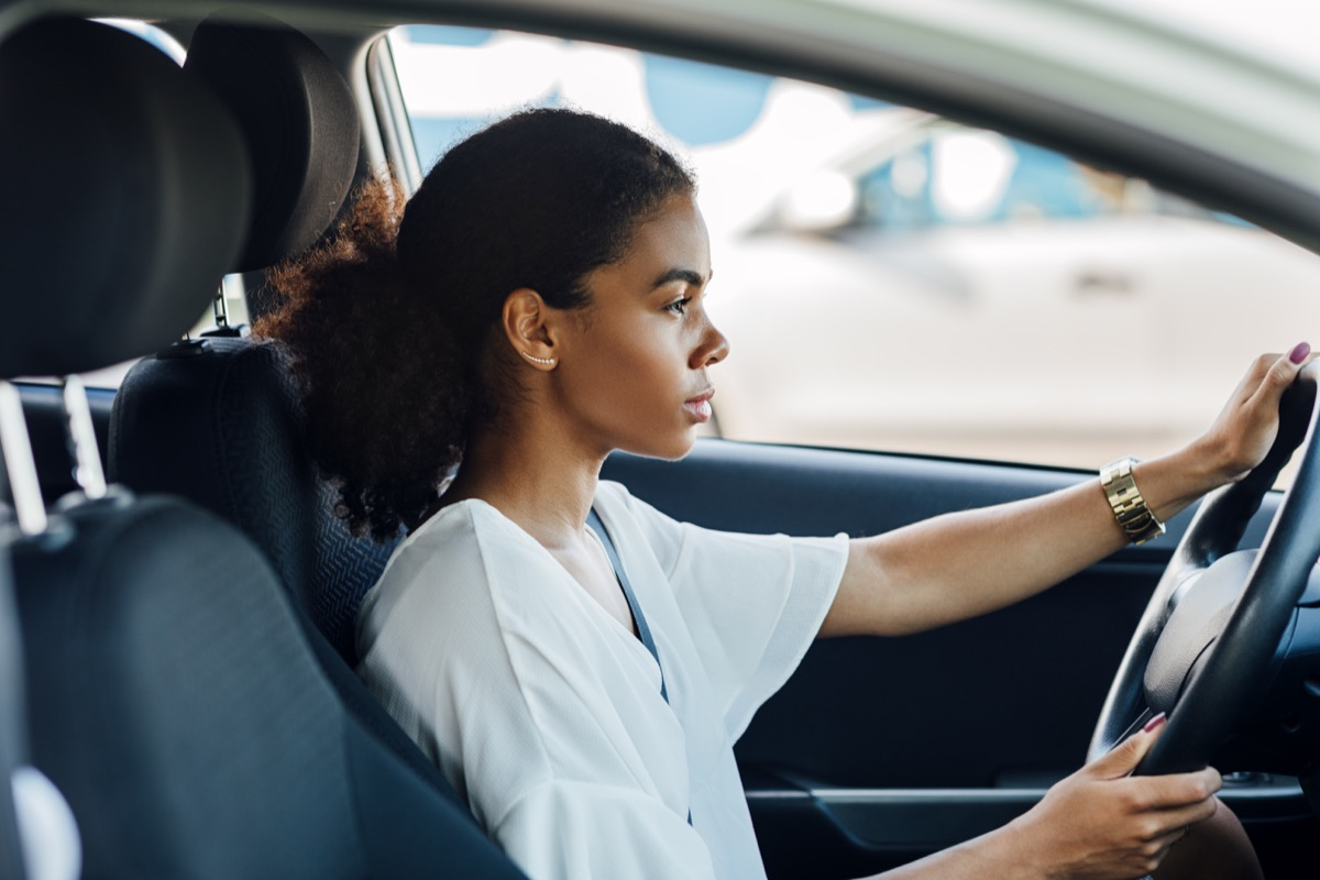 Side view of a woman sitting in a car holding a steering wheel and looking on the road