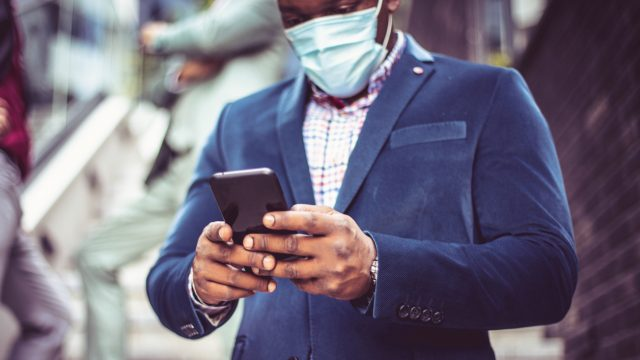A man wearing a blue blazer and protective face mask checks his smartphone.