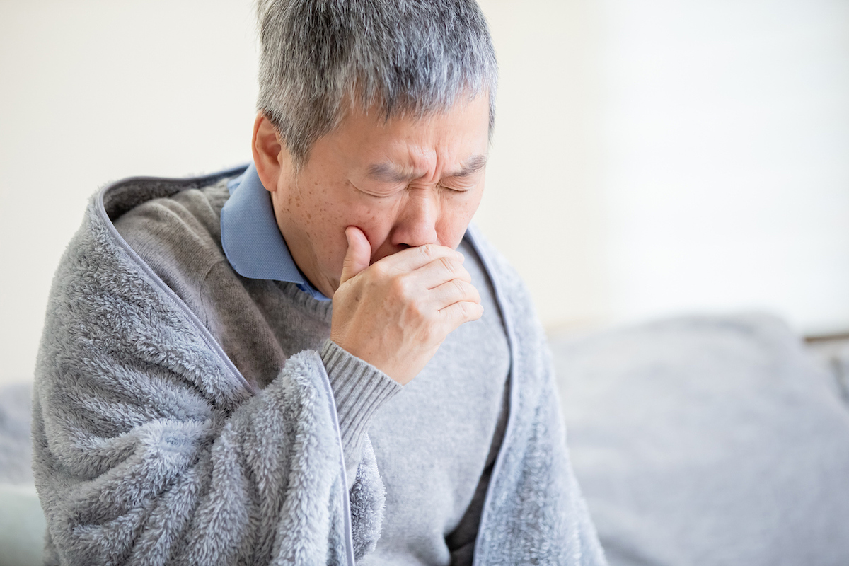 Elderly sick man has a cough at home