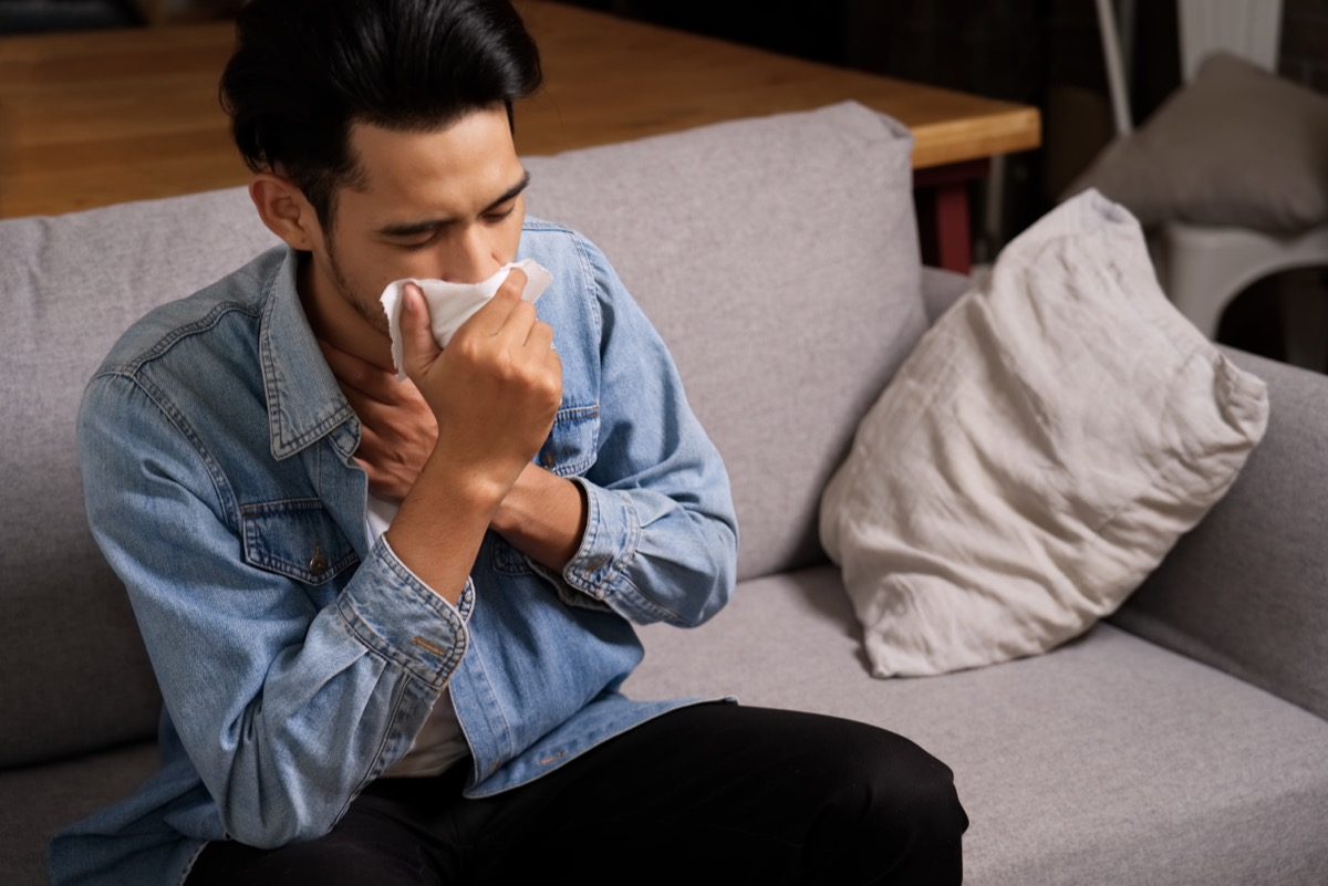 young man in denim shirt coughing into tissue