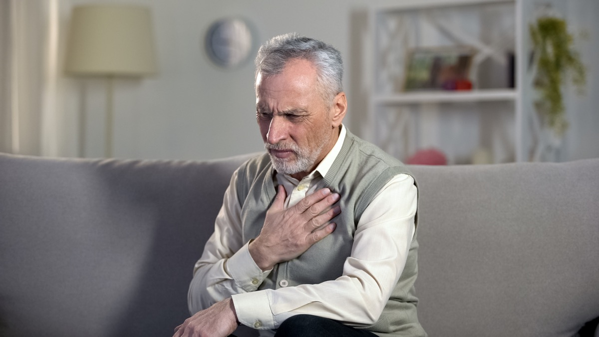 man having difficulty breathing and holding his chest