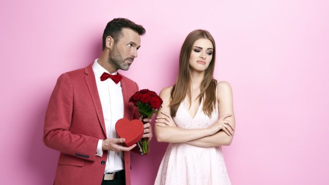 man giving a woman flowers and a heart box and woman looking displeased