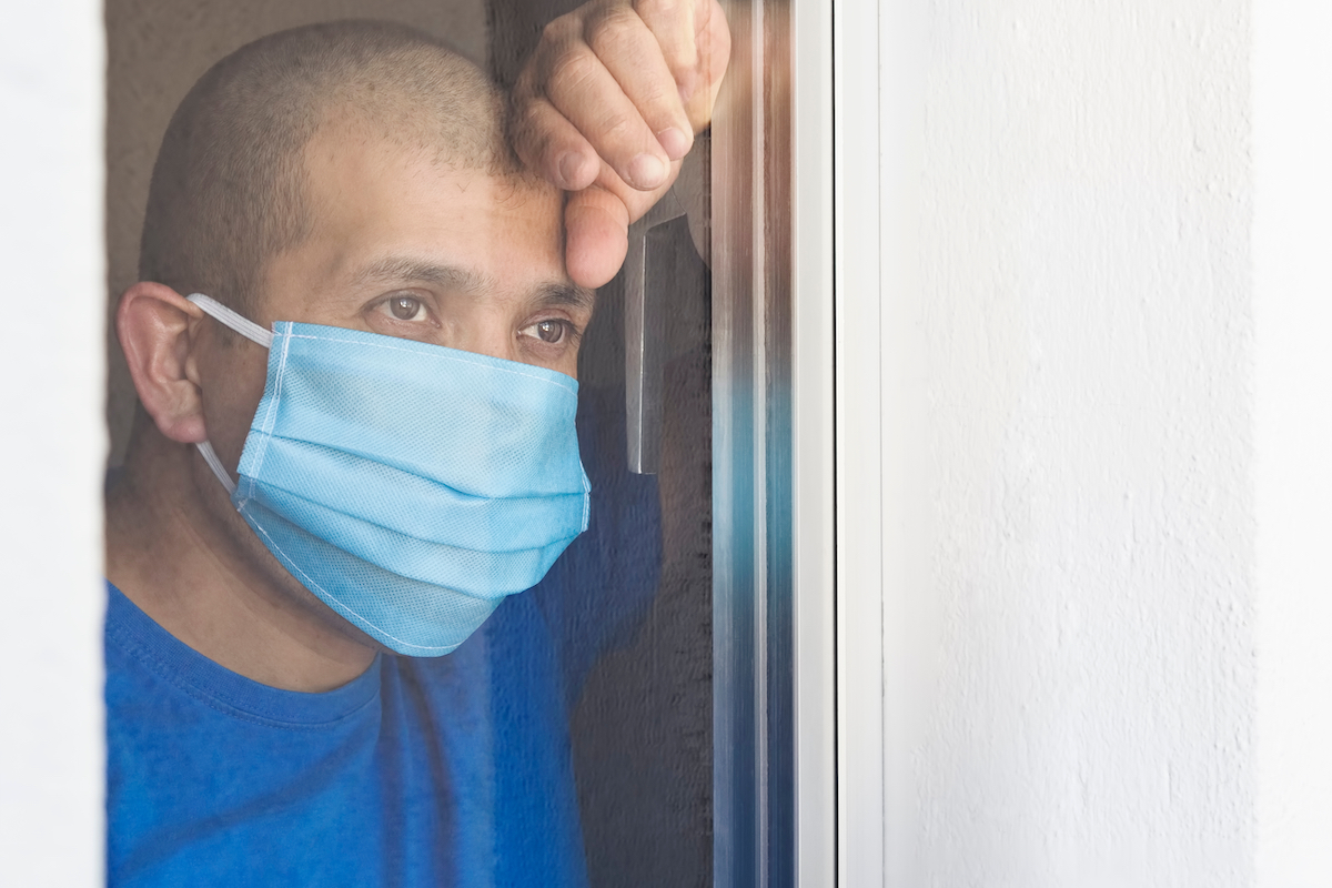 Sick man with face mask looking out the window being quarantined at home.