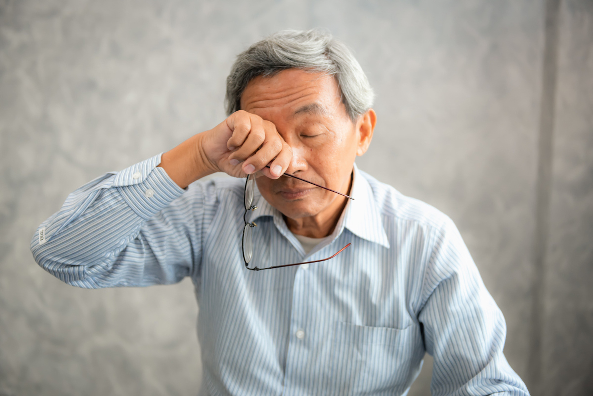 Senior man is holding eyeglasses and rubbing his tired eyes while reading e-book in tablet.