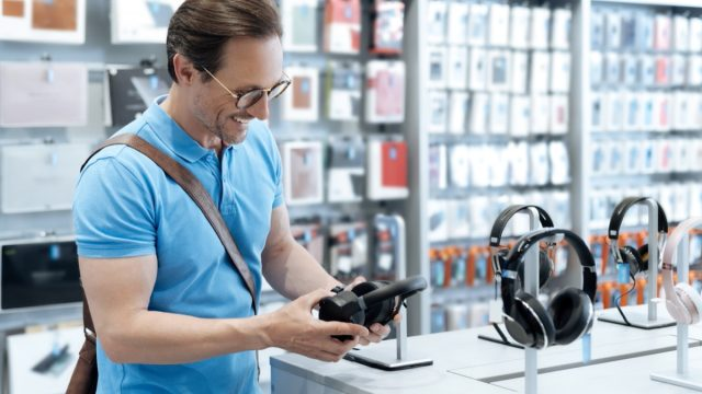 man shopping for headphones at electronics store