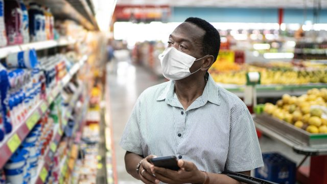 Mature man in mask using mobile phone and choosing products in supermarket, potentially for Super Bowl party
