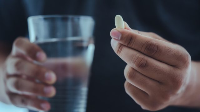 man holding a pill in one hand and glass of water in another