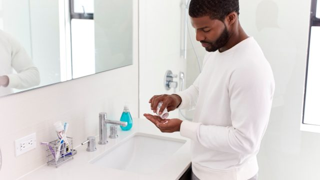 young man in white shirt standing in white bathroom taking vitamins out of a pill bottle in his hand
