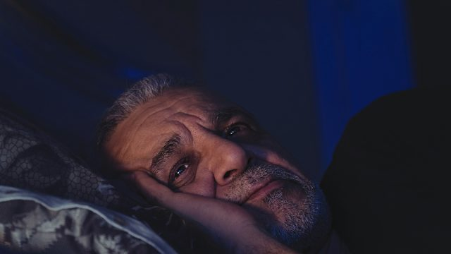 Elderly man can't sleep, lays awake in bed with eyes open, looking deep in thought