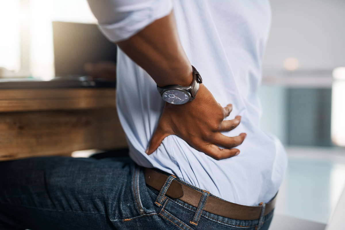 Man suffering from back pain while trying to work in the office