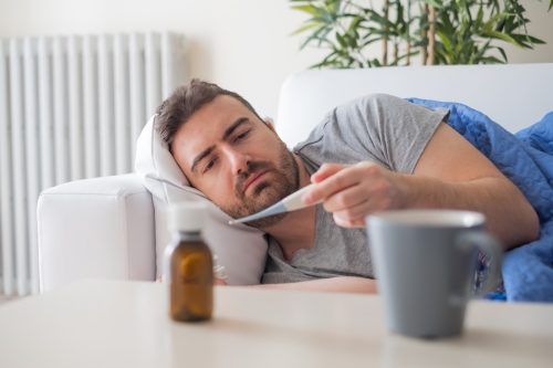 Sick man checking temperature and feeling bad at home