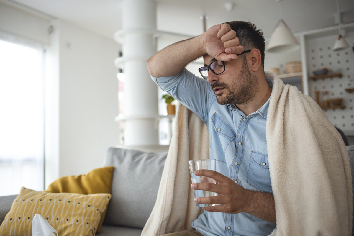 Young man suffering with fever and chills while sitting wrapped in a blanket on the sofa at home