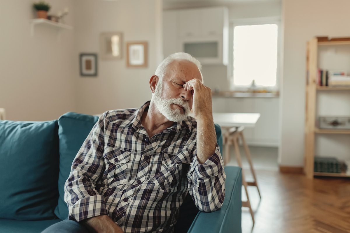 Senior Man Suffering From a headache While Sitting on the sofa in the Living Room