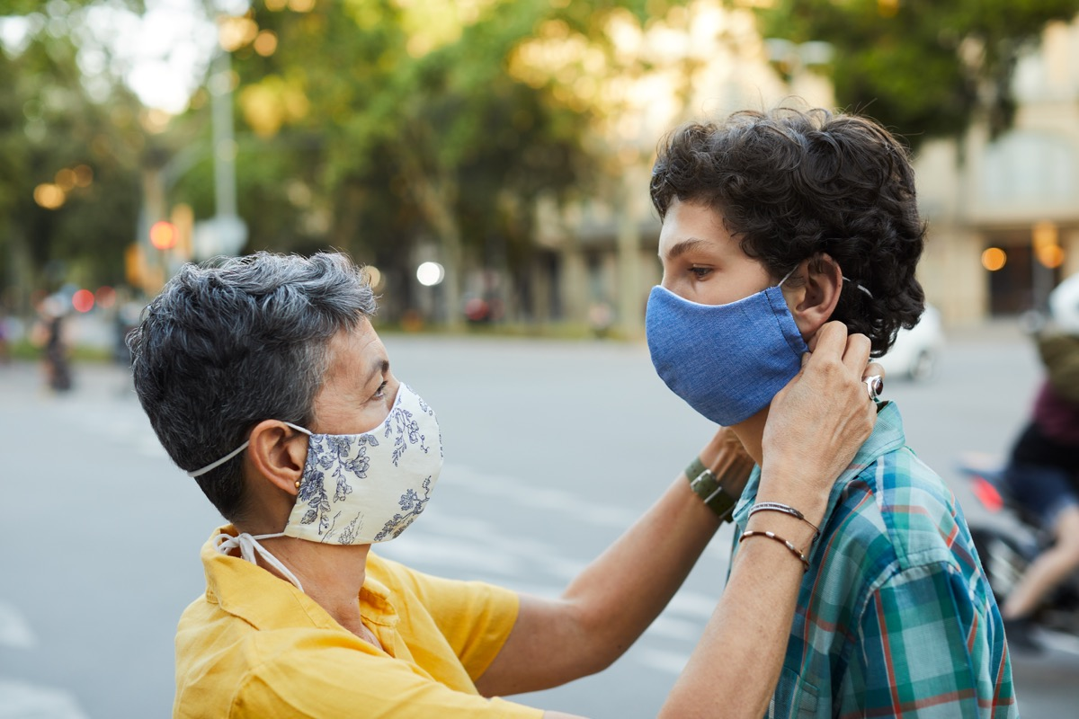 A caring mother is adjusting her teenager son's COVID mask