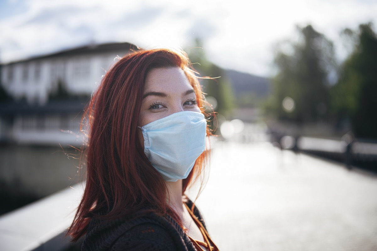 Portrait of woman with red hair wearing protective face mask outdoor and smiling in camera, looking at camera.