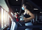 Active fitness woman wearing hygienic protective face mask while training in gym to protect herself and others against coronavirus or covid-19. Stay safe and healthy.