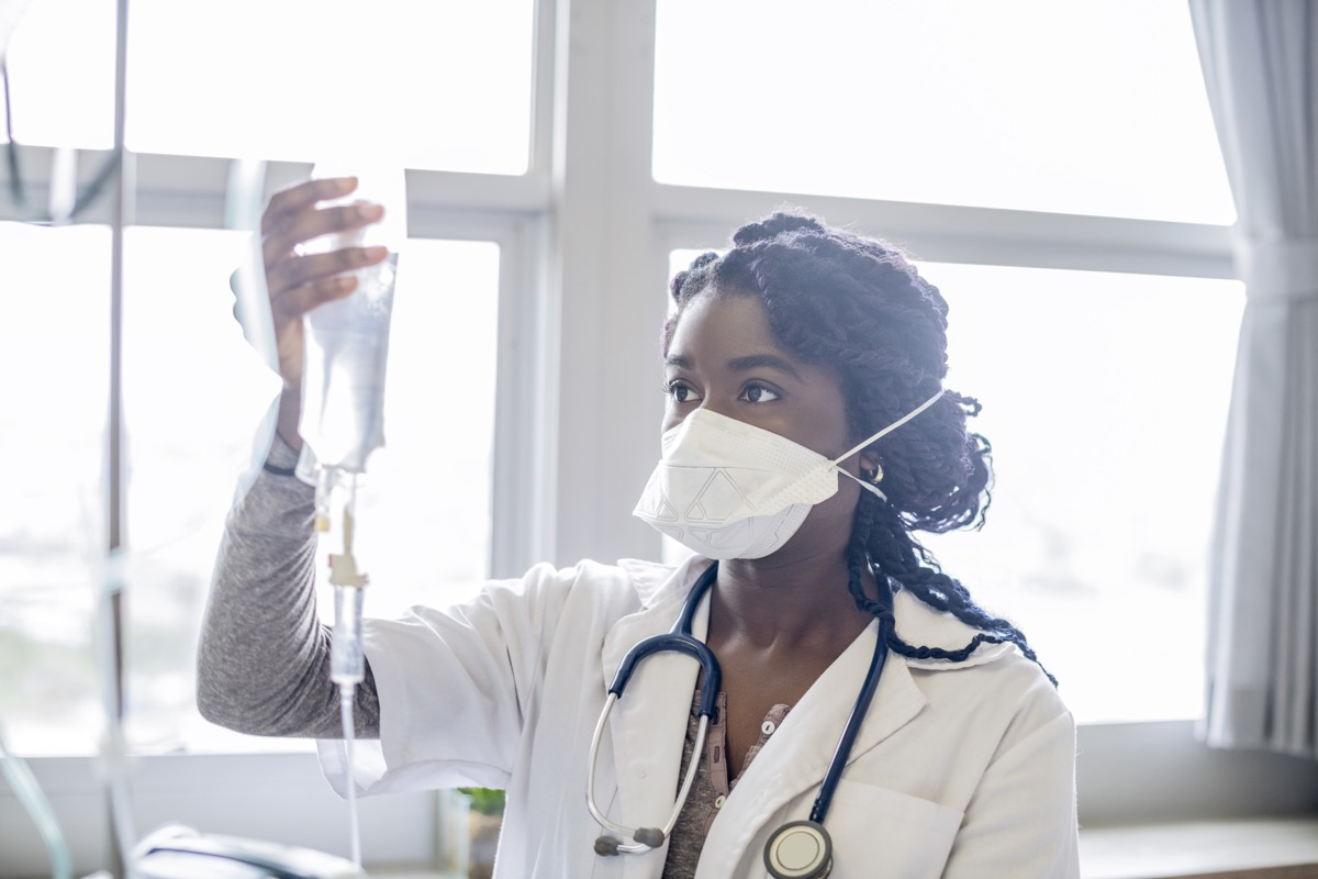 Female doctor working in hospital, holding intravenous drip, accuracy, protection, care