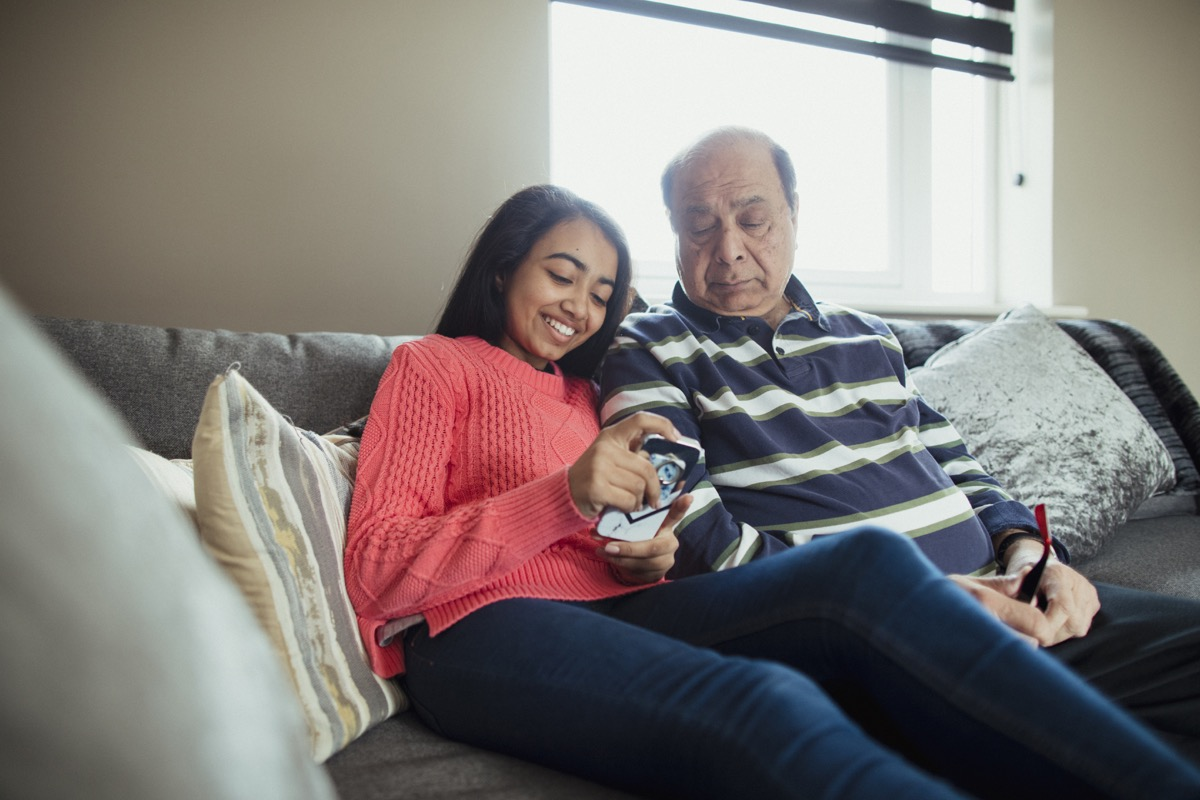 A front-view shot of a grandfather sitting down on a sofa with his granddaughter, the young granddaughter is using her phone to play an online game.