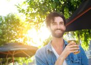 Man smiling drinking outside