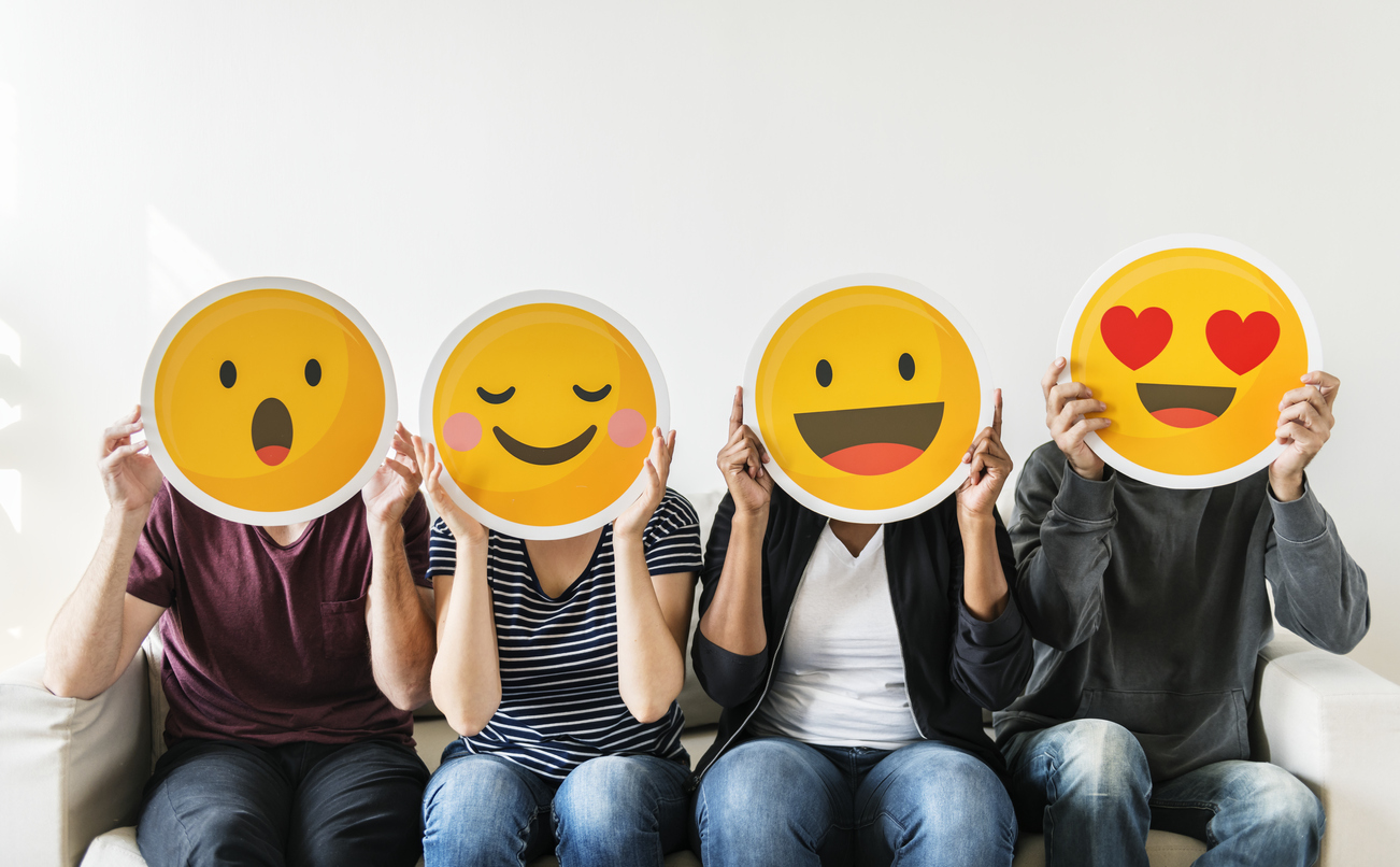 Four people sitting on a couch each holding a different reaction emoji cut out in front of their faces.