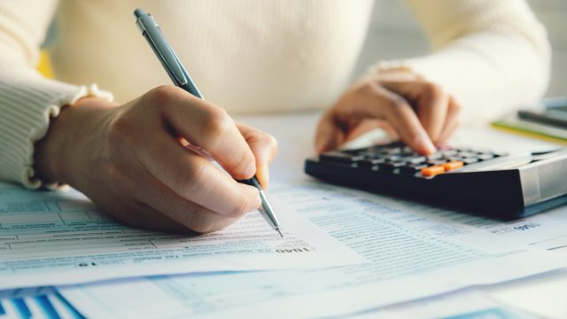A person sitting and filling out their personal income tax forms while using a calculator